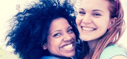 afro hair girl with blonde, best friends happy together hugging and laughing. 2 multi-cultural girls strong friendship concept. smiling and embracing.