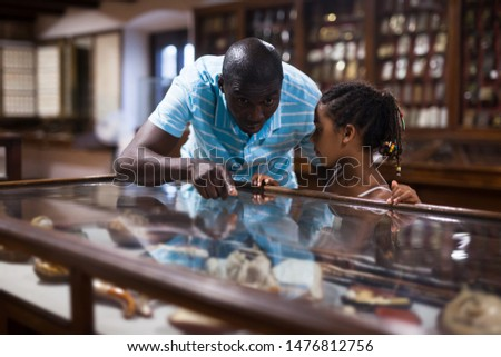 Afro male visitor and his little daughter visiting museum and looking at showcase with exhibits