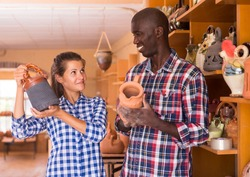 Afro man and European woman choosing earthenware in souvenir shop