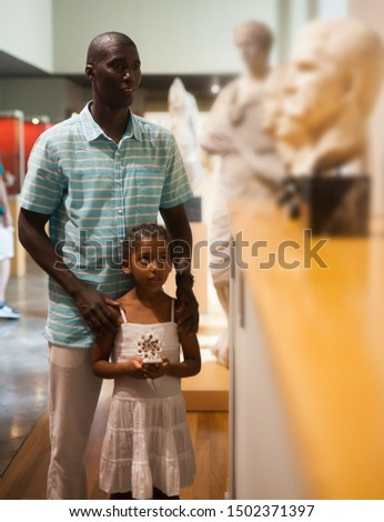 Afro man and his little daughter visiting exposition of Art Museum with exhibits of antiquity