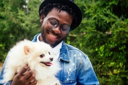 afro man hugging his fluffy spitz in park