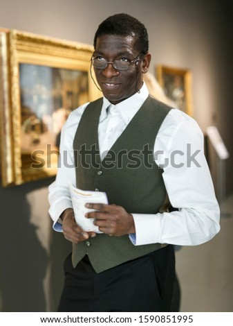 Afro man wearing glasses visiting exposition of museum with exhibits of painting