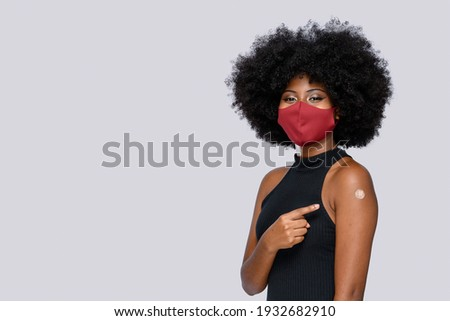 afro teenager girl happily shows the vaccine brand in background gray