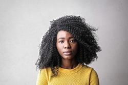 Afro woman in yellow sweater