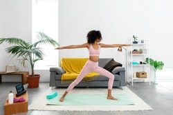 Afro woman practicing Warrior II pose using online yoga training program in the tablet at home