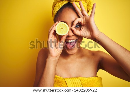 Afro woman wearing towel after shower holding slice lemon over isolated yellow background with happy face smiling doing ok sign with hand on eye looking through fingers