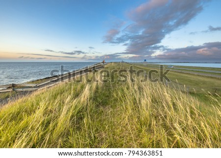 Afsluitdijk dutch dike with fences motorway and cycling track during  sunset with clouded sky
