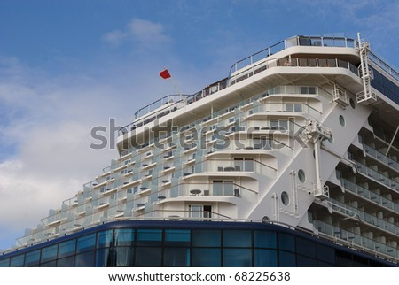Aft of a cruise ship with balconies of luxury staterooms.