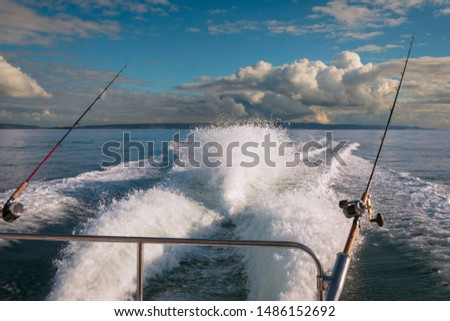 Aft view of speeding boat wake with salmon fishing rods in rod holders and cloudscape. #1486152692