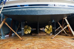 Aft with two propellers of the luxury motor yacht is dry docked on wooden blocks and supported by steel supports.