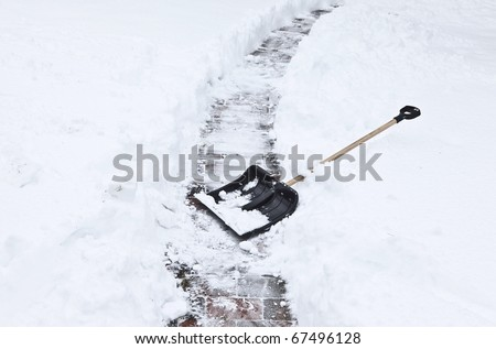 after a heavy snowstorm. black shovel to remove the snow from the garden path.