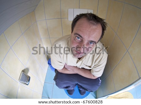 after a sleepless night with diarrhea. man sitting on toilet with diarrhea and feeling unwell. Image taken with a fish-eye lens.