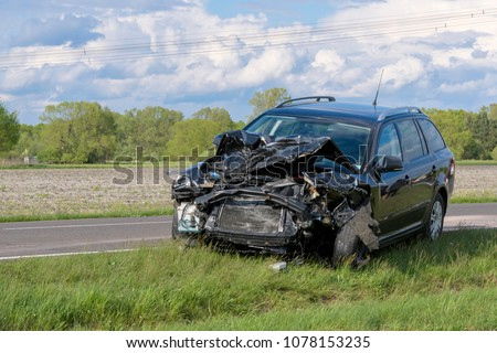 After an accident, a car is on the side of the road, probably a total loss.