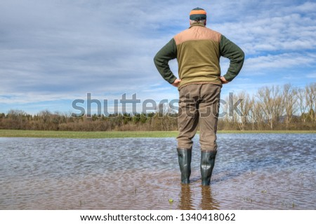 After an extremely heavy rainfall in Germany a farmer stands with his rubber boots in the middle of a huge puddler and looks at his flooded meadow. #1340418062