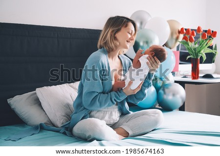 After baby delivery mother and baby at home. Mother holds her newborn in hands. Mom and baby together. Childbirth and motherhood concept. Family celebrates birth of new baby boy.