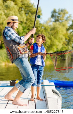 After catching fish. Handsome cheerful son feeling excited after catching fish with daddy #1485227843