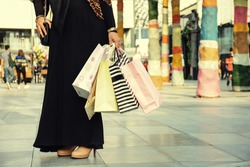 After day shopping. Close-up of young arabic woman carrying shopping bags while walking along the street, wearing abaya and hijab.