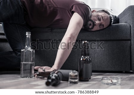 After drinking. Drunk bearded adult man lying on the sofa and sleeping after drinking lots of alcohol #786388849