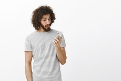After long time ex-girlfriend calling. Surprised stunned emotive guy with curly hair and beard, staring at smartphone screen with amazed expression, lifting eyebrown from unexpected message