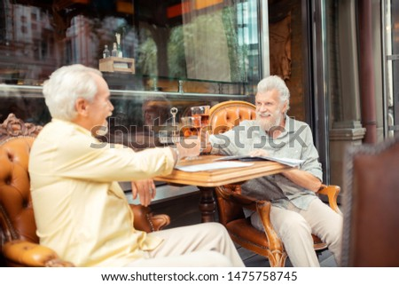 After many years. Two aged grey-haired old friends enjoying their meeting after many years