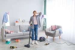 After party chaos. Dismayed millennial woman standing in her messy apartment with vacuum cleaner, holding head in terror, copy space. Terrified female student cleaning dirty university dorm room
