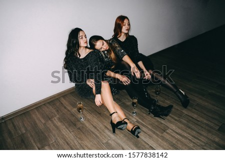 After party, jet set, clubbing, nightlife concept. Tired girls with glasses of champagne sit on the floor after celebrating party.   #1577838142