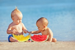 After sea swimming frolic asian baby girl and white boy have a fun and eat fruits on sand beach Healthy kids food, active lifestyle, water activity and children travel with parents on family vacation