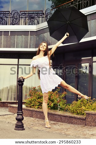 After the rain. Happy girl in a white dress with umbrella on the street