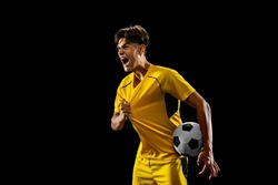 After winning game. Happy proud male football player in yellow uniform isolated over dark background. Successful competition. Concept of action, speed, energy, sport, competition and ad.