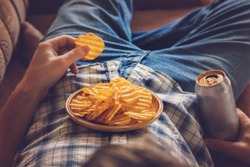 After work a guy wearing shirt and jeans lying on sofa, drinking a cold beer, eating crisps and watching sport tv channel. Man's resting time at home concept.
