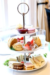 afternoon high tea with a tiered tray of decadent sandwiches, scones and desserts