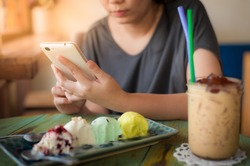 Afternoon scene of young woman using smartphone for social networking in ice cream cafe on weekend. Trendy lifestyle concept with technology.