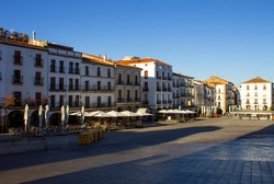 Afternoon sunlight shines on the white medieval buildings, restaurants and cafes of Plaza Mayor (main square), the wide open plaza in the centre of the historic town of Cáceres, Extramadura, Spain.