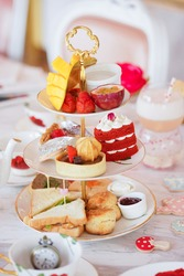 Afternoon tea. An afternoon tea time with selective focus on the red velvet cake. Fresh tropical fruits on top tier, sweet and dessert on second tier and savoury on the last tier.