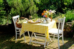 Afternoon tea served in the garden. Flowers and food tray on the white table covered with yellow tablecloth. Flower basket on the white chair.