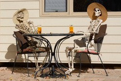 Afternoon tea shared between friends: Skeletons in hats sitting at a table outdoors