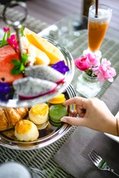 Afternoon tea with mini brioche canapes. Beautiful english afternoon tea ceremony with desserts and snacks selection of sweets