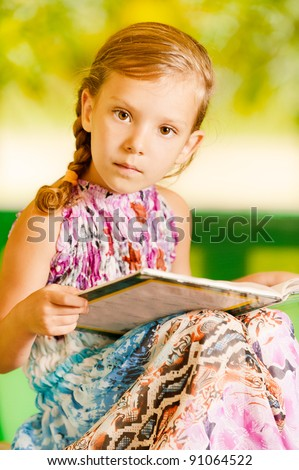 against background of green park, small, pretty, serious girl in long, bright dress, sits reading book