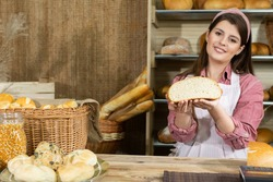 Against the backdrop of the bread shelves, a young attractive saleswoman shows a round cross-section of wheat bread. Company stand with bread.
