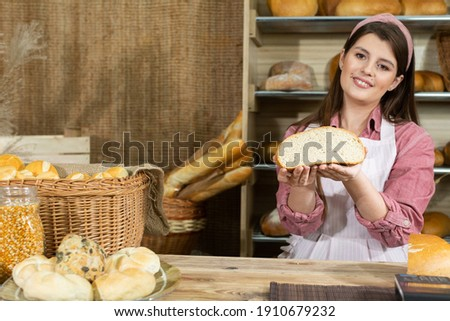 Against the backdrop of the bread shelves, a young attractive saleswoman shows a round cross-section of wheat bread. Company stand with bread. ストックフォト ©