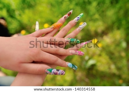 against the background of flowering branches of women's hands with a nice manicure different picture