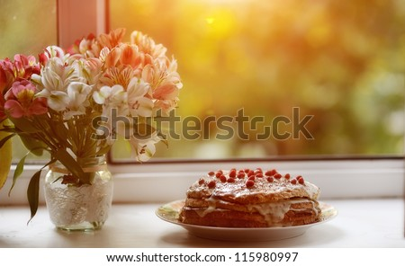 against the background of the window is a cake with berries and a bouquet of flowers near - stock photo