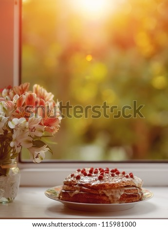 against the background of the window is a cake with berries and a bouquet of flowers near