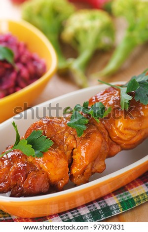 against the background of the wooden kitchen table on checkered cloth, mouth-watering meat kebab (pork, beef, lamb, chicken) on skewer in large bowl