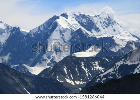 Against the blue sky, an alpine snow-capped peak, sharp rocks and peaks and ridges of the lower mountains are visible, sunny weather in the mountains in winter.