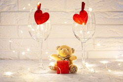 Against the white brick wall two empty wine glasses with red hearts, between the glasses sits a plush little teddy bear with a red gift box, around the glasses is a glowing garland