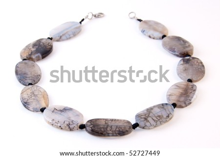 Agate necklace on white. Shallow depth of field. Focus on the closest beads.