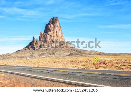 Agathla peak with the road to Monument Valley  in the foreground, Arizona, United States.