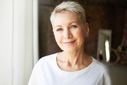 Age, beauty, wellbeing and health concept. Close up portrait of good looking beautiful mature female with gray pixie hair, blue eyes and wrinkles smiling happily at camera, being in good mood