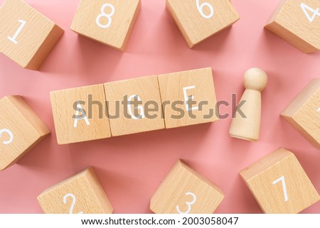 Age; Wooden blocks with 'Age' text of concept, and a human toy. Stock photo ©